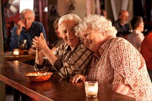 Filmstill CLOUDBURST, Olympia Dukakis und Brenda Fricker lehnen sich aneinander, an Bar in einer Kneipe