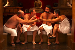 Film Still BEARCITY 2: THE PROPOSAL by director Doug Langway; a group of friends (Brian Keane, Joe Conti, James Martinez, Alex Di Dio) sit with towels in a sauna with a buddha statue in the background