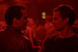 Filmstill PRAIA DO FUTURO von Karim Aïnouz, Clemens Schick und Wagner Moura stehen sich gegenüber in rotem Licht
