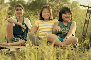 Filmstill ANITA'S LAST CHA CHA, Ang Huling Cha-Cha Ni Anita, Film von Sigrid Andrea P. Bernardo, drei grinsende Kinder auf Wiese