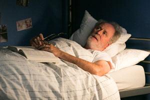 Film LOVE IS STRANGE von Ira Sachs mit Marisa Tomei, Alfred Molina und Cheyenne Jackson; Schauspieler John Lithgow liegt im Bett mit Buch auf dem Schoß