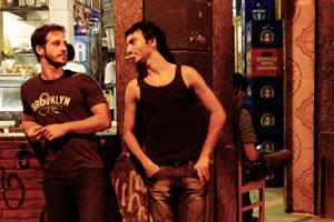 Filmstill AYA ARCOS, Daniel Passi spricht mit einem Mann vor einem Restaurant