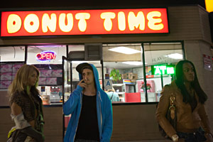 Filmstill TANGERINE L.A. von Sean Baker, Alexandra (Mya Taylor), Sin-Dee (Kitana Kiki Rodriguez) und Zuhälter Chester (James Ransone) stehen nachts vorm Donut Time