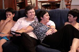 Filmstill GAYBY BABY, Matt mit seinen beiden lesbischen Müttern und seinem Bruder auf dem Sofa