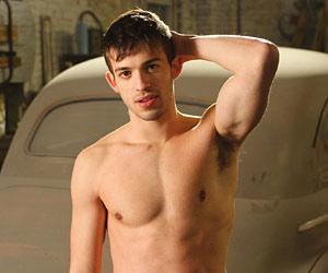 Filmstill BEAUTIFUL SOMETHING – WIE SCHÖN DU BIST, Zack Ryan als Jim posiert mit nacktem Oberkörper vor Auto