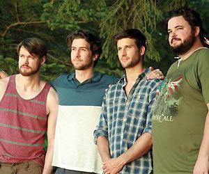 Film Still 4TH MAN OUT von Andrew Nackman. Nick (gespielt von Chord Overstreet), Adam (gespielt von Evan Todd), Chris (gespielt von Parker Young) und Ortu (gespielt von Jon Gabrus) stehen im Wald
