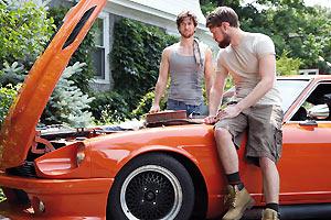 Film Still 4TH MAN OUT von Andrew Nackman mit Evan Todd, Jon Gabrus, Parker Young und Chord Overstreet. Adam (gespielt von Evan Todd) und Nick (gespielt von Chord Overstreet) stehen an einem heißen, orangefarbenen Auto