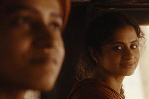 Film Still QISSA – DER GEIST IST EIN EINSAMER WANDERER von Anup Singh mit Irrfan Khan und Tisca Chopra, die als Junge aufgezogene Kanwar (gespielt von Tillotama Shome) und ihre Verlobte Neeli (gespielt von Rasika Dugal) liegen voneinander abgewandt auf dem Bett