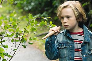Film-Still CLOSET MONSTER von Stephen Dunn mit Connor Jessup, Aliocha Schneider und Isabella Rossellini; der junge Oscar läuft mit einem Holzpflock in der Hand herum