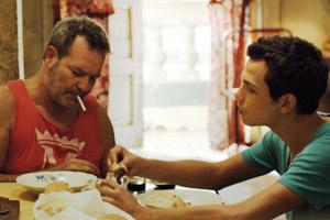 Film Still VIVA von Paddy Breathnach mit Héctor Medina, Jorge Perugorría, Luis Alberto García und Renata Maikel Machin Blanco; Jesús (gespielt von Héctor Medina) und sein Vater Angel (Jorge Perugorria) sitzen zusammen am Essenstisch
