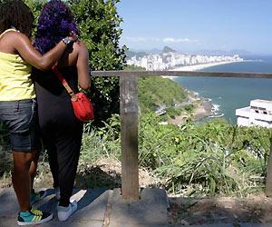 Film Still FAVELA GAY (NRW-Premiere) von Rodrigo Felha; ein lesbisches Pärchen steht über dem Strand-Panorama von Rio de Janeiro
