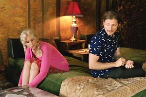 Film Still I LOVE YOU BOTH von und mit Doug Archibald; Donnys Zwillingsschwester Krystal (gespielt von Kristin Archibald) sitzt mit gepacktem Koffer auf dem Bett zusammen mit Andy (gespielt von Lucas Neff) auf einem Bett