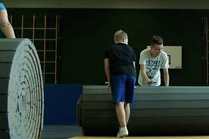Film Still JENSEITS VON ROSA UND HELLBLAU von Marcus Gerhard Preis; der transsexuelle Nuka rollt mit Mitschüler eine Matte in der Sporthalle auf