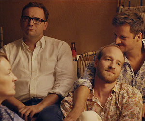 Film Still KATER - TOMCAT von Händl Klaus; das schwule Paar Stefan (gespielt von Lukas Turtur) und Andreas (gespielt von Philipp Hochmair) sitzen zärtlich aneinander gekuschelt mit Freunden zusammen