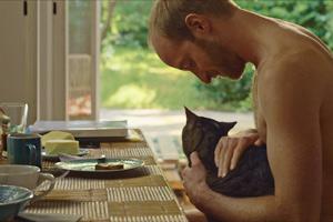 Film Still KATER - TOMCAT von Händl Klaus mit Lukas Turtur und Philipp Hochmair; Stefan (gespielt von Lukas Turtur) sitzt mit Kater am Frühstückstisch
