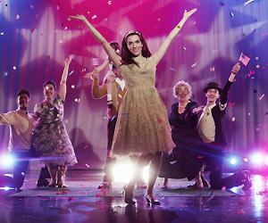 Film Still LIBERTY'S SECRET – THE 100% ALL-AMERICAN MUSICAL von Andy Kirshner & Debbie Williams; Liberty Smith (gespielt von Jaclene Wilk) tanzt überschwänglich bei Konfetti und Scheinwerferlicht  vor einem Vorhang, der in den Farben der US-Flagge beleuchtet ist