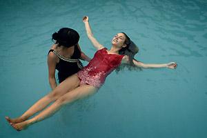 Film Still POOL – PISCINA von Leandro Goddinho; ein Mädchen hilft einem anderen, auf dem Wasser zu treiben