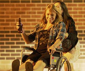 Film Still SKIN DEEP von Jon Leahy; Leah (gespielt von Zara Zoe) schiebt eine lachende Caitlin (gespielt von Monica Zanetti) in einem Rollstuhl durch die Nacht