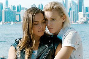 Film Still BELOW HER MOUTH von April Mullen; Jasmine (gespielt von Natalie Krill) und Dallas (gespielt von Erika Linder) sitzen vor einer Kulisse aus Fluss und Stadt-Skyline