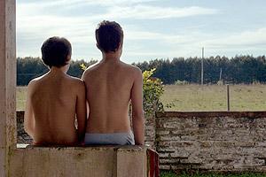 Film Still ESTEROS von Papu Curotto mit Esteban Masturini und Ignacio Rogers; Matías und Jerónimo sitzen als Kinder vor einer grünen Wald- und Wiesen-Landschaft