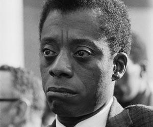 Film Still I AM NOT YOUR NEGRO von Raoul Peck und James Baldwin, erzählt von Samuel L. Jackson;  Autor James Baldwin sitzt mit ernstem Gesicht in einer Menschengruppe