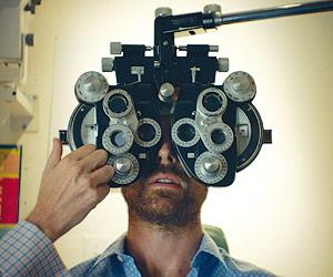 Film Still AUF DEN ZWEITEN BLICK – LAZY EYE von Tim Kirkman mit Lucas Near-Verbrugghe und Aaron Costa Ganis; Hauptcharakter Dean sitzt beim Augenarzt und bekommt seine Augen vermessen.