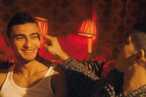 Film Still BRÜDER DER NACHT von Patric Chiha; zwei junge Roma sitzen in einer Bar mit roten Lampen und einer zeigt mit dem Zeigefinger auf die Augenbraue des anderen