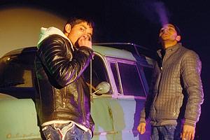 Film Still BRÜDER DER NACHT von Patric Chiha; zwei junge Roma rauchen nachts vor einem grünen Auto