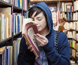 Film Still TAKE ME FOR A RIDE – UIO: SÁCAME A PASEAR von Micaela Rueda; Schülerin Sara (gespielt von Samanta Caicedo) steckt in einer Bibliothek ganz wörtlich die Nase in ein Buch