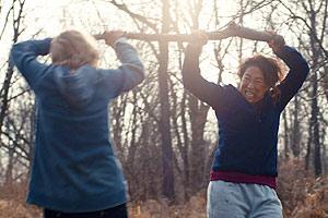Film Still CATFIGHT von Onur Tukel; mit Alicia Silverstone, Tituss Burgess, Catherine Curtin; Ashley (gespielt von Anne Heche) und Veronica (gespielt von Golden-Globe-Gewinnerin Sandra Oh) prügeln sich um und mit einem großen Ast im Wald