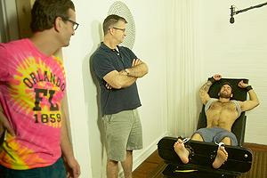 Film Still TICKLED von David Farrier und Dylan Reeve; die Regisseure sehen einen Kitzelteilnehmer, der auf einer Pritsche gefesselt ist