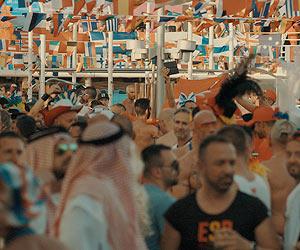 Film Still DREAM BOAT von Tristan Ferland Milewski; Berlinale-Dokumentarfilm über eine schwule Kreuzfahrt; internationale Passagiere tanzen unter einem Baldachin aus verschiedenen Länderflaggen