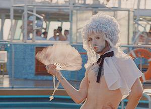 Film Still DREAM BOAT von Tristan Ferland Milewski; Berlinale-Dokumentarfilm über eine schwule Kreuzfahrt; Passagier an Deck in Rococo-Drag-Kostüm mit Fächer