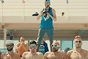 Film Still DREAM BOAT von Tristan Ferland Milewski; Berlinale-Dokumentarfilm über eine schwule Kreuzfahrt; vier sexy Kerle sitzen mit Sonnenbrillen nebeneinander und ein Fotograf steht hinter ihnen