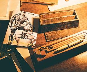 Film Still TOM OF FINLAND von Dome Karukoski mit Jakob Oftebro, Werner Daehn und Pekka Strang; Zeichenmaterial und ein Magazin mit einer Zeichnung von Tom of Finland auf dem Cover
