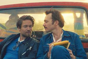 Film Still TOM OF FINLAND von Dome Karukoski mit Jakob Oftebro, Werner Daehn und Pekka Strang; der junge Tuoko alias Tom sitzt mit einem Freund bei Sonnenuntergang auf der Ladefläche eines Pickup-Trucks