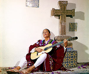 Film Still CHAVELA von Catherine Gund und Daresha Kyi über die lateinamerikanische Ranchera-Sängerin Chavela Vargas mit Pedro Almodóvar; Chavela sitzt im Poncho vor einem Steinkreuz und spielt Gitarre