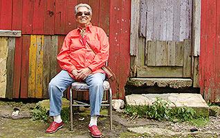 Film Still CHAVELA von Catherine Gund und Daresha Kyi über die lateinamerikanische Ranchera-Sängerin Chavela Vargas mit Pedro Almodóvar; Chavela sitzt mit Sonnenbrille vor einer Holzhütte