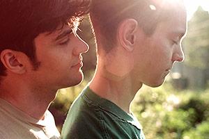 Film Still FERAL - erste Staffel von Morgan Jon Fox; Billy (gespielt von Jordan Nichols) schmiegt sich von hinten an seinen Freund Carl (gespielt von Ryan Masson)