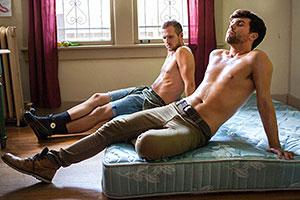Film Still FERAL - erste Staffel von Morgan Jon Fox; Daniel (gespielt von Seth Daniel) kuschelt oberkörperfrei mit seinem Freund CQ (gespielt von Jacob Rickert) auf dem Bett