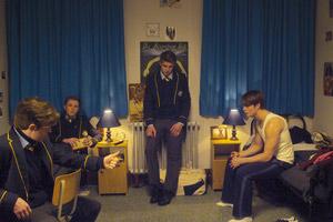 Film Still HANDSOME DEVIL von John Butler; Conor Masters (gespielt von Nicholas Galitzine) sitzt rechts auf seinem Bett, während seine Rugby-Freunde in Schuluniform zusammensitzen