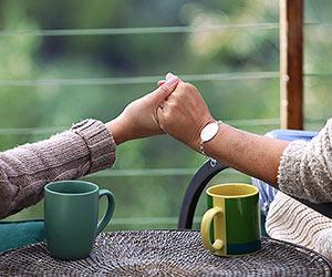 Film Still MILLIONEN MOMENTE VOLLER GLÜCK – A MILLION HAPPY NOWS von Albert Alarr; Detailaufnahme, wie Lainey Allen (gespielt von Crystal Chappell) und ihre Lebenspartnerin Eva Morales (gespielt von Jessica Leccia) sich bei den Händen halten auf der Terrasse mit zwei Kaffeetassen auf dem Tisch