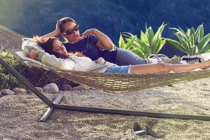 Film Still MILLIONEN MOMENTE VOLLER GLÜCK – A MILLION HAPPY NOWS von Albert Alarr; Lainey Allen (gespielt von Crystal Chappell) und ihre Lebenspartnerin Eva Morales (gespielt von Jessica Leccia) liegen zusammen in einer Hängematte