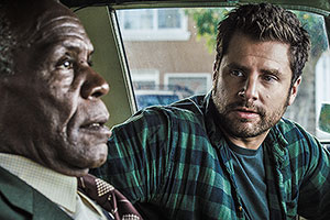 Film Still PUSHING DEAD von Tom E. Brown mit James Roday, Danny Glover, Robin Weigert, Khandi Alexander und Tom Riley; Dan Schauble (gespielt von Roday) dreht sich im Auto zu Kneipier Bob (gespielt von Glover) um