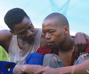 Film Still DIE WUNDE - THE WOUND - INXEBA von Regisseur John Trengove; Vija (gespielt von Bongile Mantsai) sitzt neben Xolani (gespielt von Nakhane Touré) und legt seinen Arm um ihn