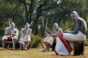 Film Still DIE WUNDE - THE WOUND - INXEBA von Regisseur John Trengove; eine Gruppe von jugendlichen Xhosa sitzt mit traditioneller Bekleidung, Holzstäben und weißer Bemalung zusammen
