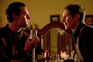 Film Still B&B BnB von Joe Ahearne mit Paul McGann; Marc (gespielt von Tom Bateman) und Pension-Betreiber Josh (gespielt von Paul McGann)sitzen sich demonstrativ gegenüber