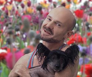 Film Still BEZIEHUNGSKONTO von Autor, Regisseur, Produzent, Komponist und Hauptdarsteller Roland Schimmel-Pfennig aus Köln; Roland (gespielt von Roland Schimmel-Pfennig)  steht mit einem nackt geschorenen Hund vor einem kunterbunten Blumenfeld