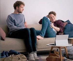 Film Still CAS von Joris van den Berg mit Kevin Hassing, Wieger Windhorst und Felix Meyer; Pepijn (gespielt von Windhorst) sitzt auf dem Sofa neben Cas (gespielt von Meyer) und beobachtet ihn