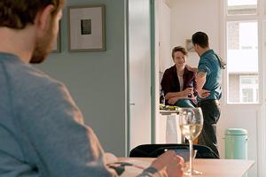 Film Still CAS von Joris van den Berg mit Kevin Hassing, Wieger Windhorst und Felix Meyer; Pepijn (gespielt von Windhorst) steht mit einer Freundin bei einer Privatparty in der hellen Küche